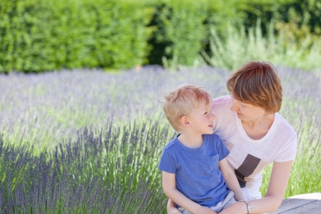 young beautiful mother and her adorable son spending time together at blooming lavender fields photo