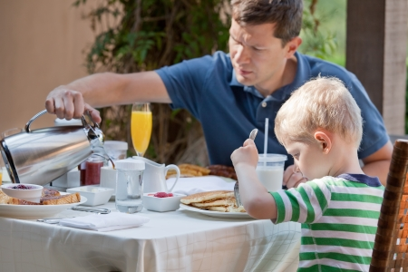 family of two eating nicely served breakfast outside; handsome young man pouring some coffee and his cute son eating delicious pancakes at breakfast time photo