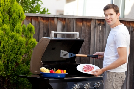 handsome young man ready for grilling meat and vegetables photo