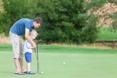 lesson: young handsome father teaching his little son how to play golf