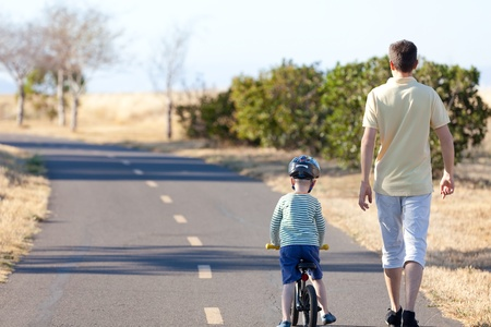 little boy and his father having a nice walk together at summer photo