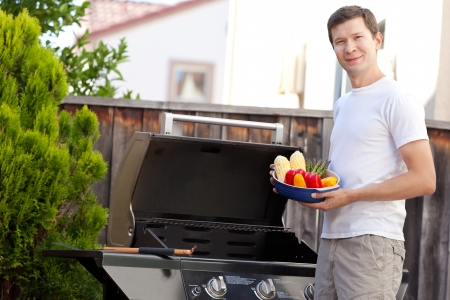smiling handsome man ready for grilling vegetables photo