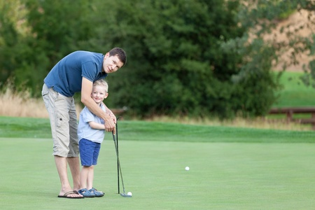 young father and his happy smiling son playing golf together photo