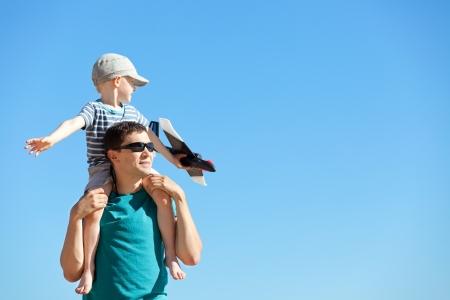 affectionate action: apuesto joven padre y su hijo lindo jugar un juguete plano exterior