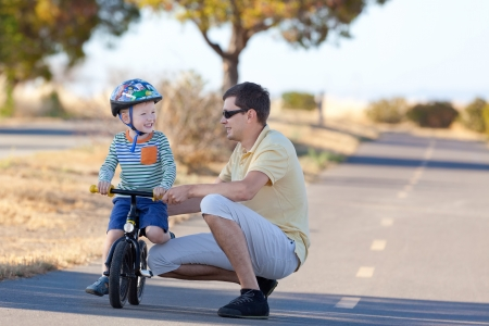 happy laughing son at the balance bike and his handsome father spending fun time together at the park photo