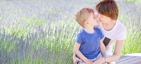happy family of mother and son touching each other with noses and spending fun time together at lavender field photo