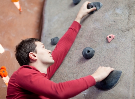 handsome young man rock climbing indoors photo
