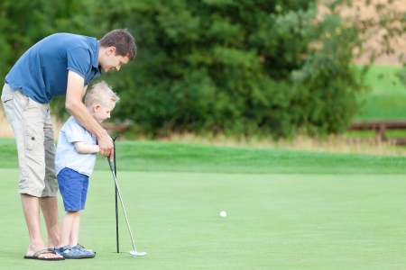 handsome father and his cute son playing golf together photo