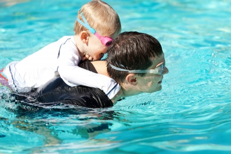 laughing cute son playing and swimming with his handsome young father at the pool photo