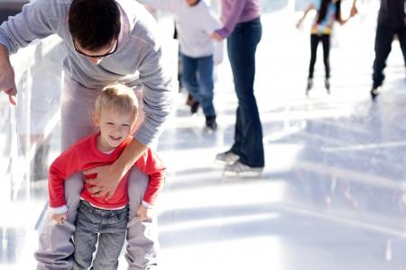 niño en patines: joven padre enseña a su pequeño hijo de patinaje sobre hielo, sonríe y tener tiempo de diversión
