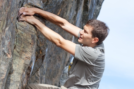 bouldering: handsome young man bouldering or rock climbing outdoors