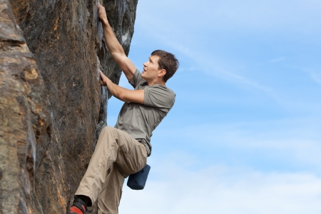 handsome young man bouldering or rock climbing outdoors Stock Photo - 21820618