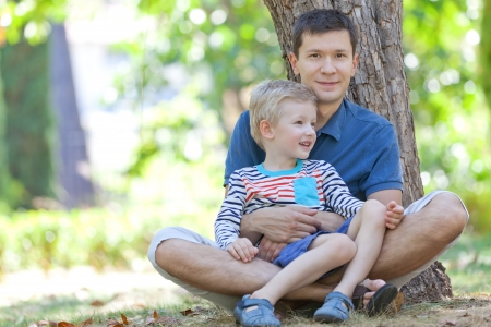 enjoying: handsome smiling father and his cute son sitting together in the woods Stock Photo