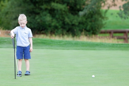 focused little boy learning to play golf photo