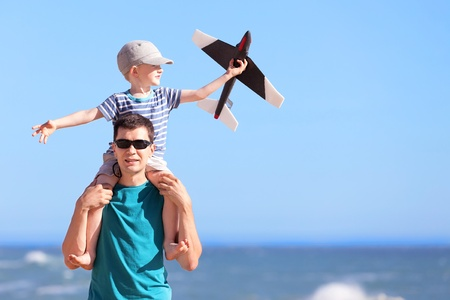 smiling positive young man and his excited son sitting on fathers shoulders and playing a toy plane at the beach photo