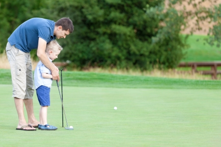 playing golf: handsome young father teaching his cute son to play golf