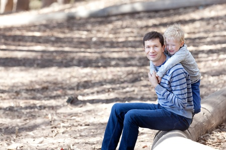handsome young father and his laughing adorable son spending time together during the hike in the woods photo