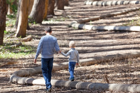 young father and his cute son walking and hiking in the woods photo