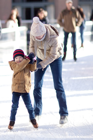 ICE RINK: happy excited little boy and his young mother learning ice-skating