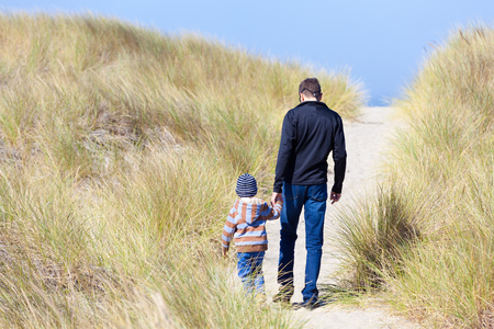 family of father and son walking on the sandy beach trail in bandon, oregon photo