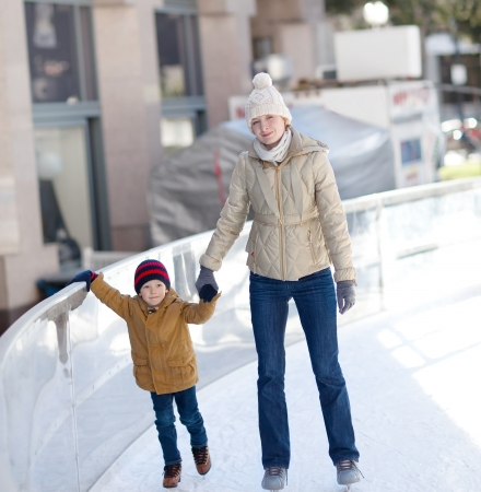 smiling beautiful mother and her cute little son ice skating together photo