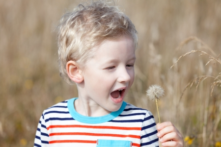 cute positive boy at summer blowing the dandelion photo