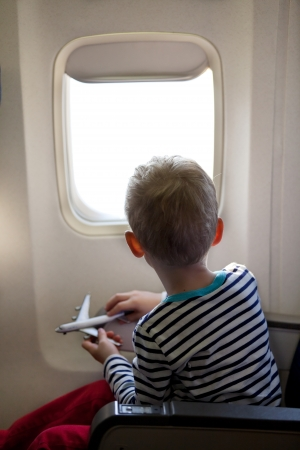little boy sitting inside the plane and playing with his toy plane photo