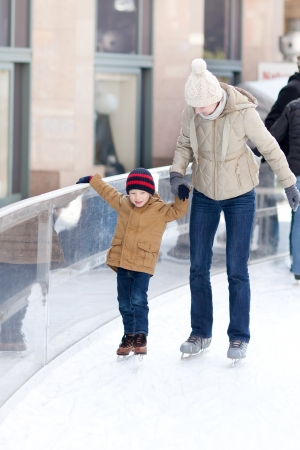 family of young mother and her son skating at winter photo