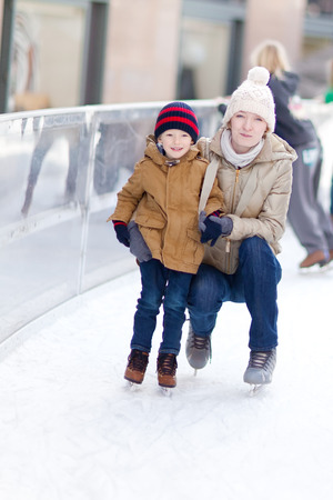 family of smiling young mother and her little son at skating rink photo