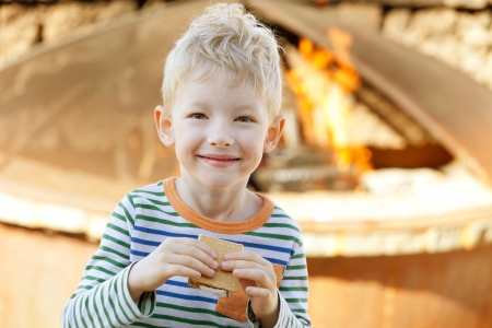 smiling cute little boy eating smores photo