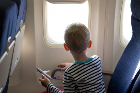 look inside: little boy in the plane looking out the window Stock Photo