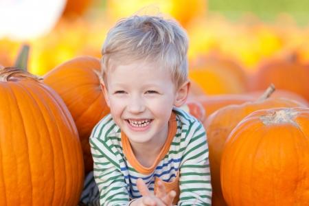 fall festival: cute smiling boy having fun at the pumpkin patch