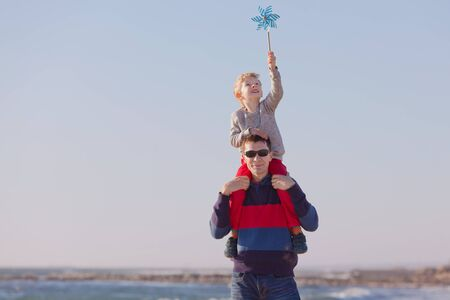cute smiling boy and his young father playing with pinwheel outside photo
