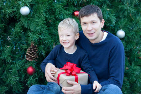 cheerful smiling boy and his father with gift box at christmas time photo