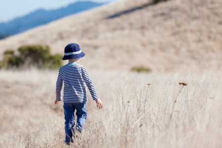 autism: little boy enjoying beautiful weather alone outdoors