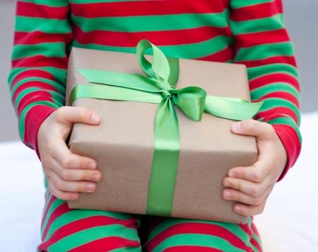 child holding a christmas present nicely wrapped Reklamní fotografie