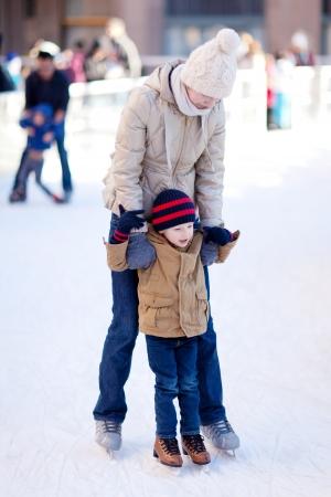 niño en patines: familia de dos personas disfrutando de hielo de invierno patinar juntos
