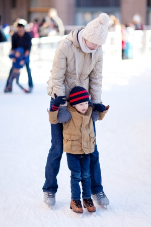 family of two enjoying winter ice skating together photo