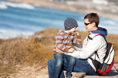 family of young happy father and cute laughing boy at the beach in california, usa photo