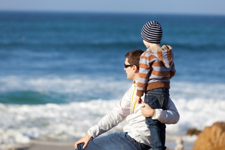 family of smiling positive boy and his young handsome father spending fun time together at the beach and looking at the ocean Reklamní fotografie