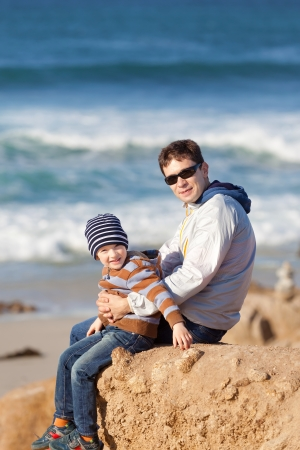 family of smiling positive boy and his young handsome father spending fun time together at the beach photo