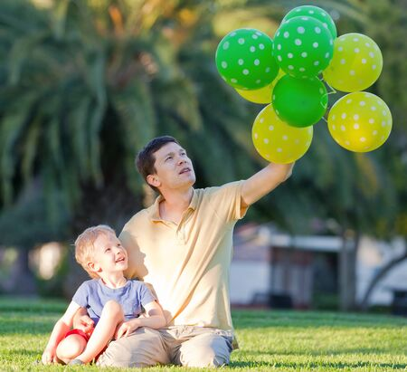 happy family of father and his son with colorful balloons photo