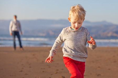 positive cheerful son running away from his father at the beach in california photo