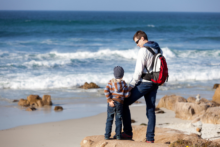 family of two spending time together by the ocean and enjoying the view photo