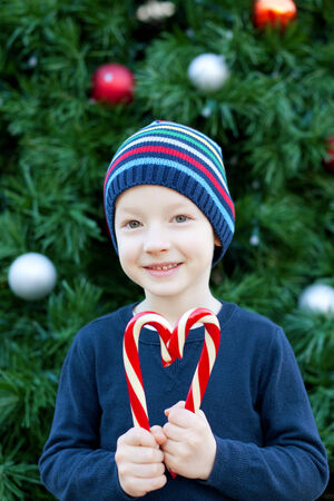 little cheerful boy making a heart shape from candy canes at christmas time photo