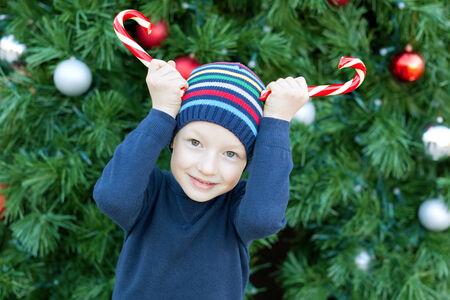 little cheerful boy making horns with candy canes at christmas time photo
