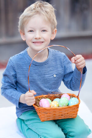 cute smiling boy with easter colorful eggs in the basket at spring photo