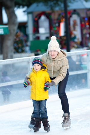 happy positive family of two ice skating at winter photo