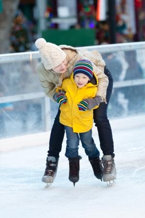 niño en patines: feliz familiar positiva de dos de patinaje sobre hielo en el invierno Foto de archivo