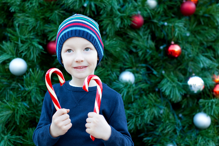 cute cheerful boy with candy canes by the christmas tree photo